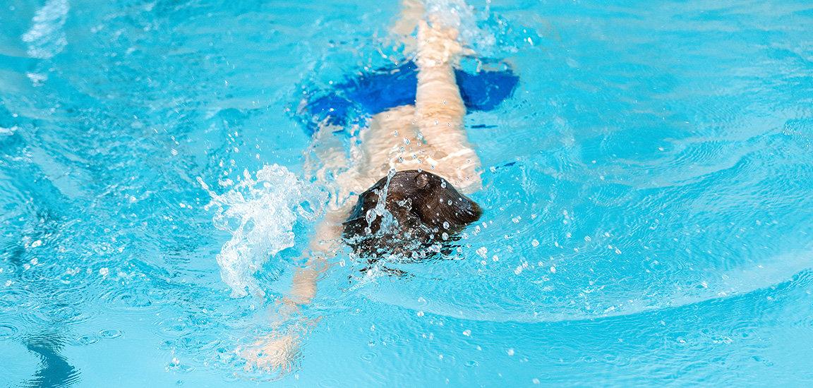 Kind am Kraulen. Schwimmen im Kinderschwimmkurs.