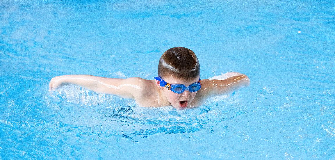 Kinderschwimmen mit Let's Swim. Kind schwimmt Delfin Schwimmstil.