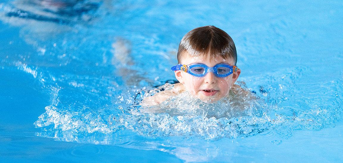 Kind mit Schwimmbrille am Schwimmen im Kinderschwimmkurs.