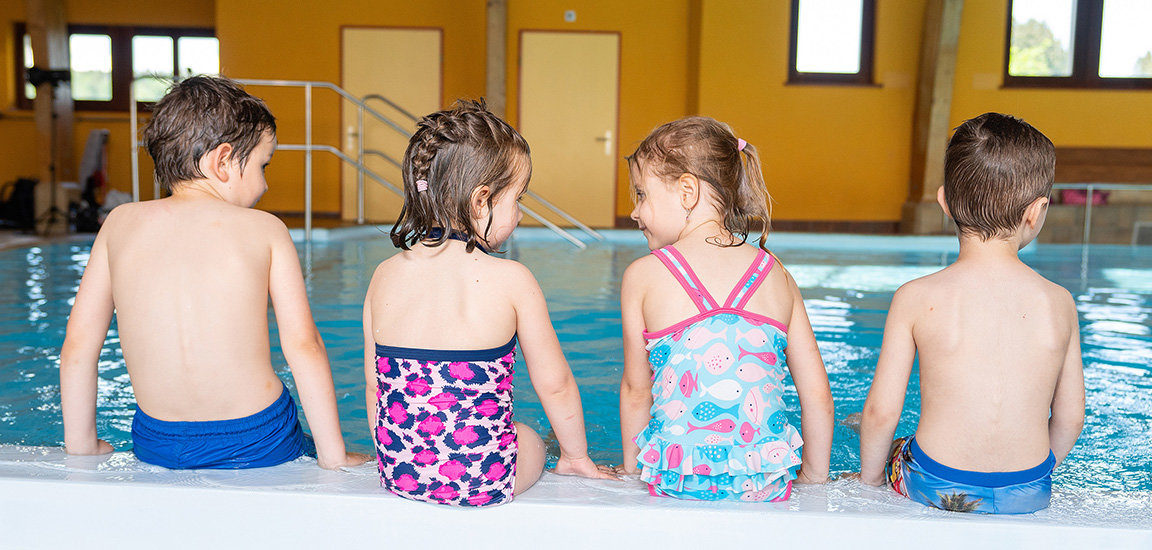 Kinder am Wasser sitzend. Kinderschwimmen mit Let's Swim.