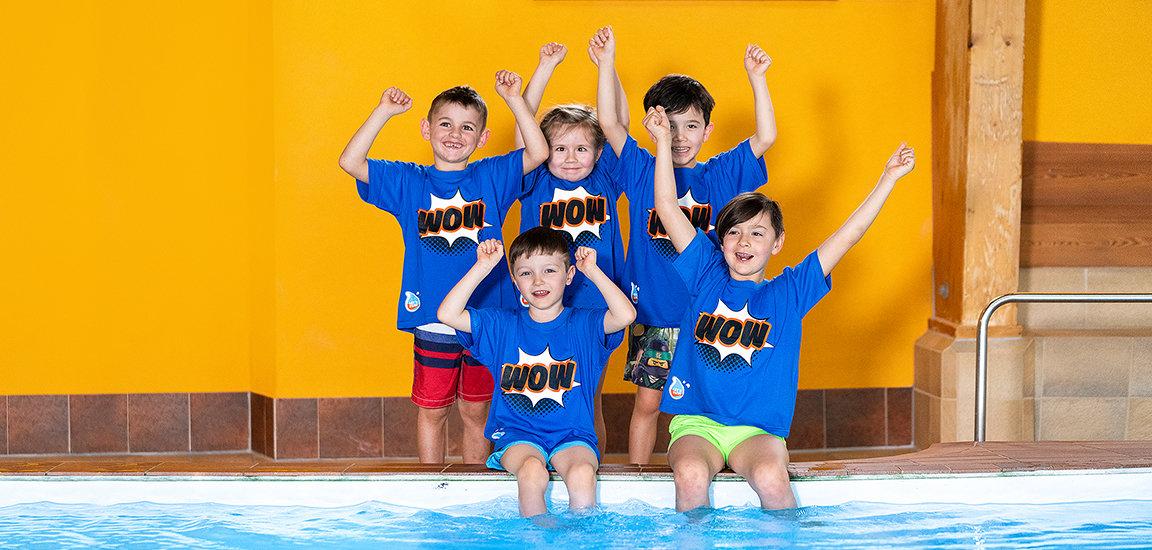 Jubelnde Kinder am Wasser im Kinderschwimmkurs.