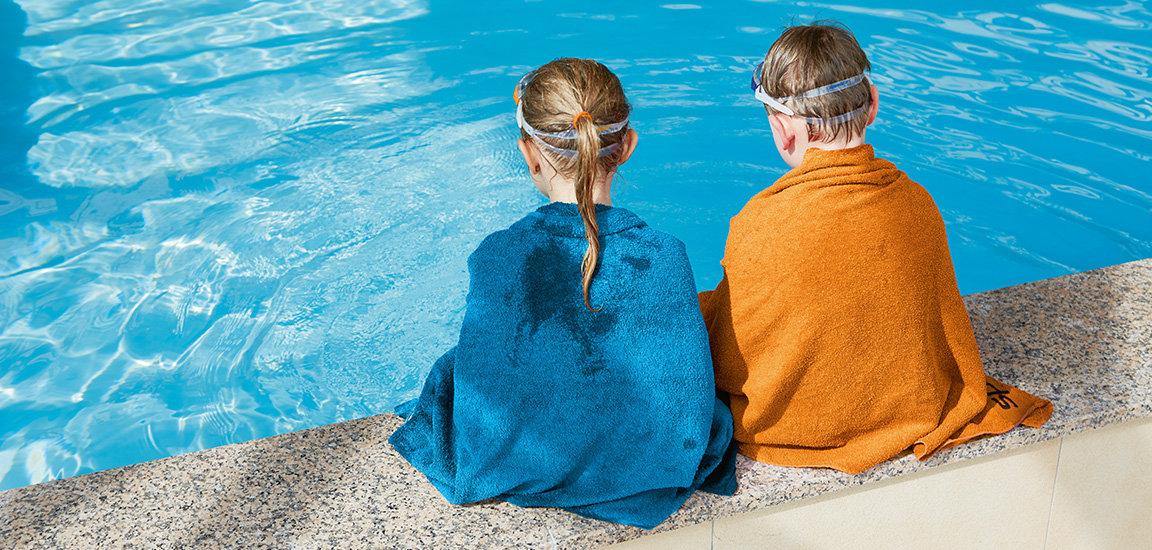 Kinder mit Badetuch am Wasser. Kinderschwimmen bei Let's Swim.