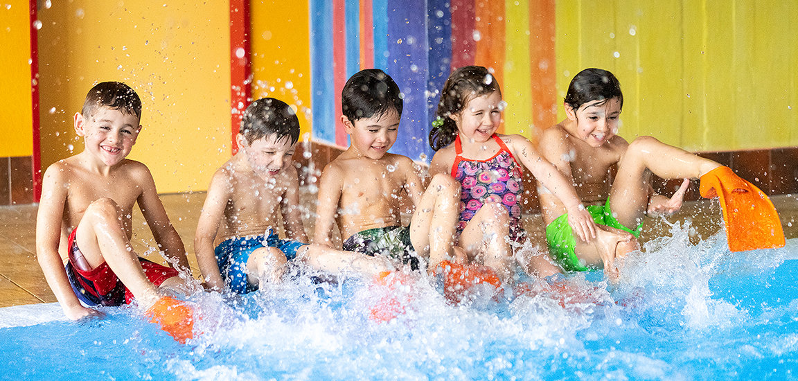 Kinder im Wasser mit Flossen. Planschende Kinde im Kinderschwimmkurs.