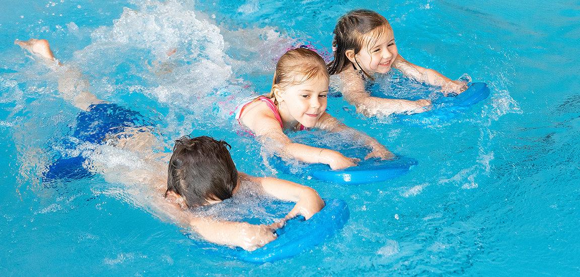 Kinder schwimmen mit Schwimmbrett bei Let's Swim.