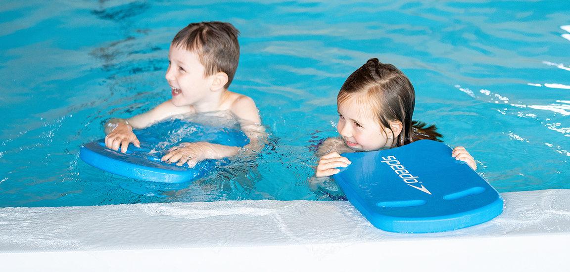 Lachende Kinder im Wasser mit Schwimmbrett. Kinderschwimmen bei Let's Swim.